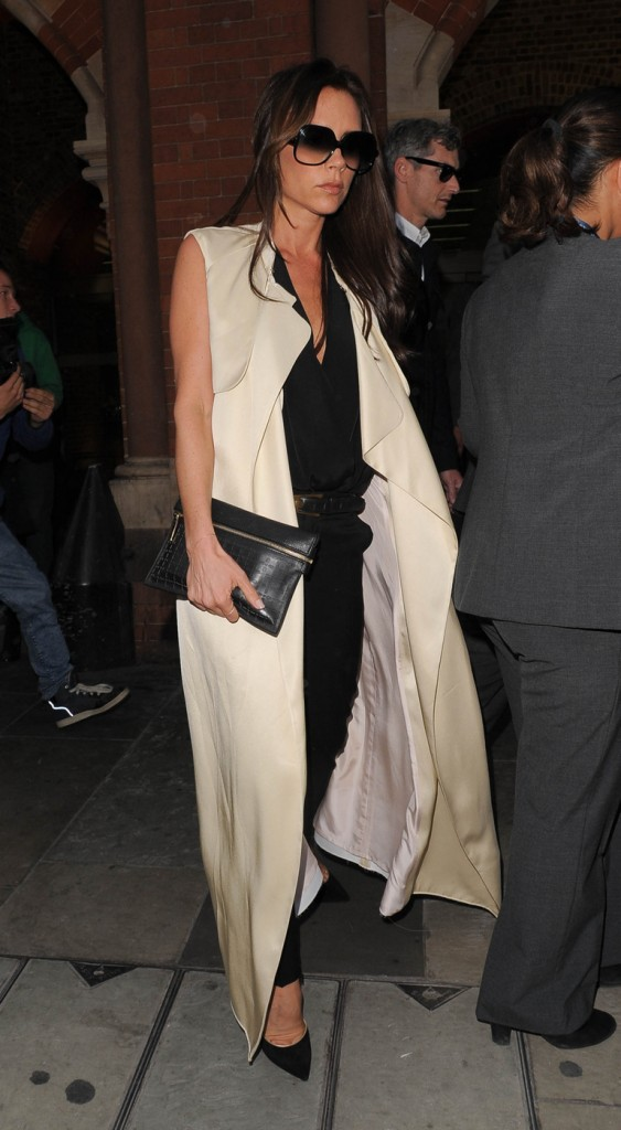 Victoria Beckham, wearing a long sleeveless jacket, arrives back in London after attending Paris Fashion Week