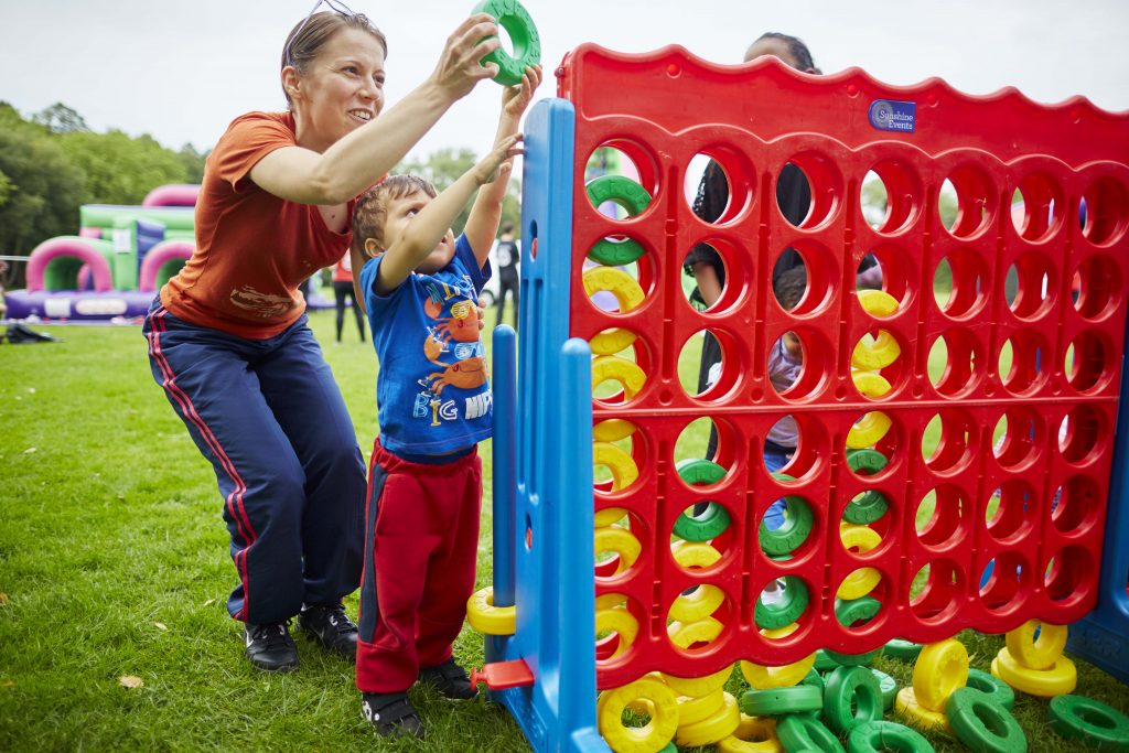 Park Lives at Alexandra Park in Moss Side Manchester Pictured Monika Meszaros 31 with son Kaniel 3 on the giant Connect Four