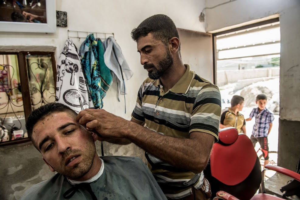 Rokam Hamoud cuts a customer's hair in his barber shop in Husseini. The shop was looted by ISIS in 2014, but support from Oxfam has helped him to rebuild the business.
