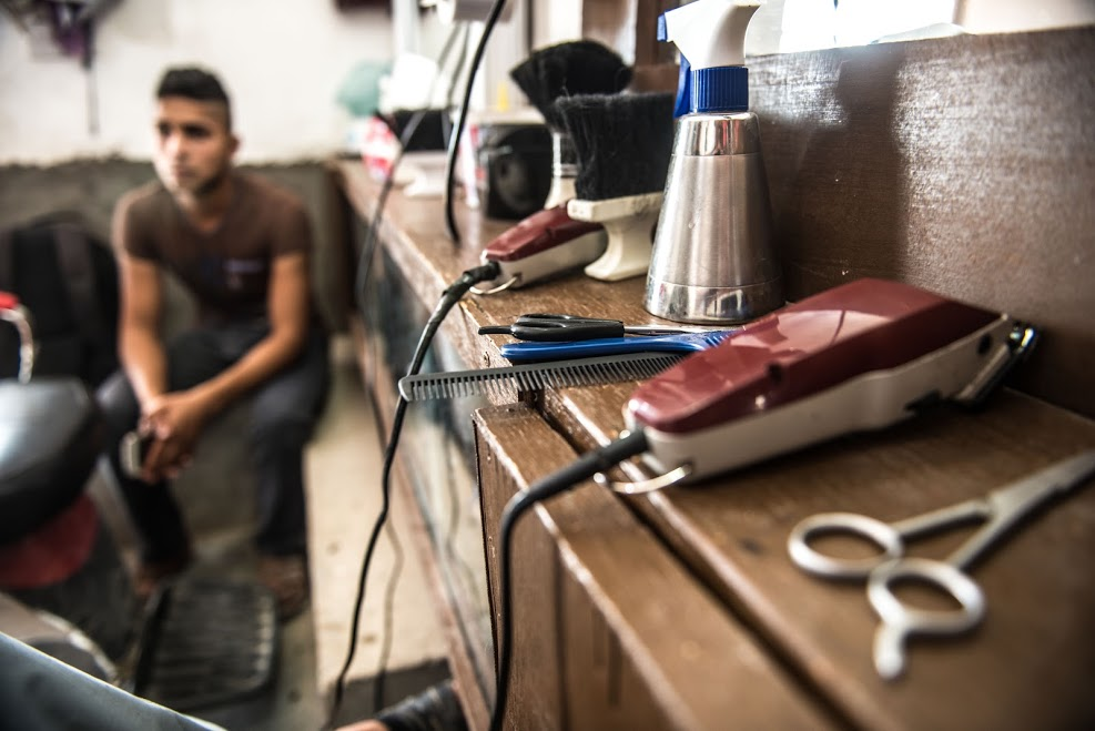 Rokam Hamoud cuts a customer's hair in his barber shop in Husseini. The shop was looted by ISIS in 2014, but support from Oxfam has helped him to rebuild the business. credit-tommy-trenchard_oxfam-may-2016-2