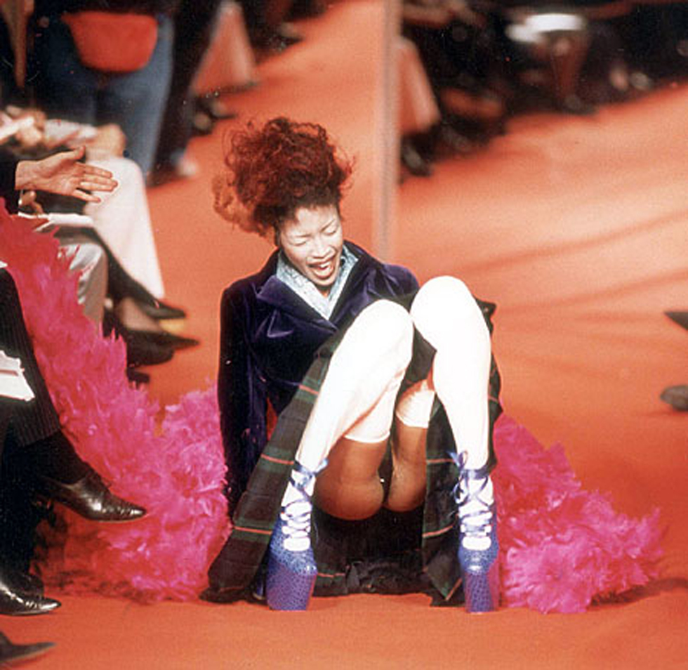 FASHION MODEL NAOMI CAMPBELL FALLS DURING THE VIVIENNE WESTWOOD FASHION SHOW IN PARIS, 1993. Poise, elegance and grace are the hallmarks of a top model. But they're wrtechedly difficult to maintain when you're totering along the catwalk in shoes with 5in platform soles and 12 in heels. Too difficult as it happened for Naomi Campbell, one of the star performers at Vivienne Westwood's stunning show during Paris Fashion Week. The 5ft 10in supermodel went form an elegant sashay to a crumpled heap in the blink of a false eyelash as she toppled over the purple, mock crocodile shoes. ...FASHION MODEL